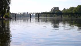 Reflection of cloudy blue sky on the surface of the river and Bridge over river. Landscape reflection of a cloudy blue sky on the surface of the river and bridge stock video footage