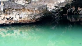 Landscape with the reflection of rocks in the water surface. Tranquil waters of underground river seek darkness under the arches of the ancient cave stock video footage