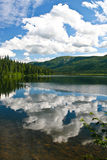 Landscape Reflections. A photo of a mountain landscape  and  clouds being reflected in a lake. The photo was taken in Alaska and is in portrait vertical format Stock Images