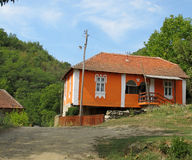 Landscape of a restored, old, traditional village house, Serbia. Landscape of a restored, old, traditional village house, with red facade and white decorated royalty free stock photos