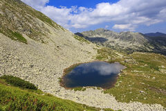 Landscape of Retezat National Park mountains  a small lake with blue sky reflection Stock Photos