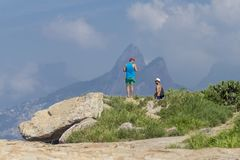 Landscape of Rio de Janeiro with two men on coastal rocks in Ipanema beach mimicking exactly the Two Brother mountain tops feature stock photos