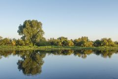 Landscape of river bank on clear summer day. Reflections of trees in water surface against blue clear sky. Natural scene nature royalty free stock photography