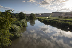 Landscape of river in countryside with blue sky reflected in water Royalty Free Stock Photo