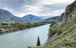 Landscape with a river flowing among mountains Royalty Free Stock Photography