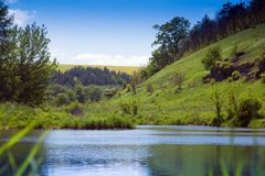 Landscape of a river, green grassy hills with trees Royalty Free Stock Image