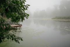 Landscape with a river in the morning mist royalty free stock photography