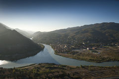 Landscape with river and mountains. Bird's eye panorama of a river, mountains and city on a bank of the river royalty free stock photo