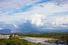 Landscape with a river and mountains. Large white cumulus clouds. Landscape with the river and mountains. Large white cumulus clouds and purple clouds royalty free stock photo