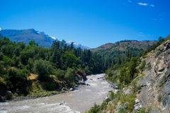 Landscape with a river mountains and trees. Beautiful landscape with a river and blue sky stock photography