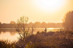 Landscape with a river, trees and a fisherman on the river bank during the sunset in warm autumn colors_ stock photography