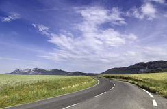 Landscape with road curve. Landscape with road, mountain and wheat fields Stock Images