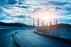 Landscape of road and oil refinery. Factory between sun rise time Royalty Free Stock Photo