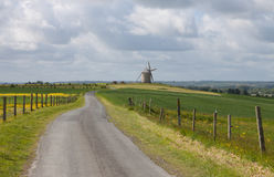 Landscape with road and windmill Stock Images