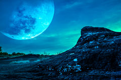 Landscape of the rock against blue sky and big moon above wilder. Landscape of rock against blue sky and big moon above wilderness area in forest. It largest stock photo