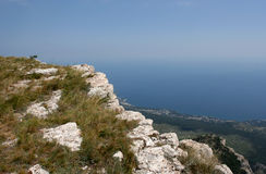 The landscape with rocks, dry grass, sea and sky. Royalty Free Stock Photography