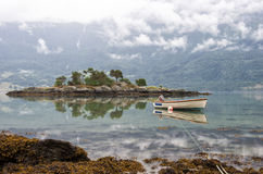 Landscape with rocky island and boat on a fjord, morning clouds and reflection in the water, Norway Stock Image
