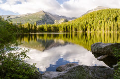 Landscape of rocky mountain glacial lake. Landscape of a glacial lake with sorrounded by mountain peak and forrest that mirrored in the water surface stock images