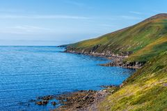 Blue sky and sea with rocky coastal line and green hills royalty free stock images