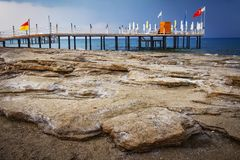 Landscape of rocky turkish beach on blue sea with pier, Konakli Turkey. seascape of stone beach in the morning. Stock Photography