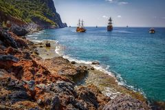 Landscape of rocky turkish beach with ships on horizon in Alanya. Scenery sea and mountains in sunny summer day at Turkey. Royalty Free Stock Image