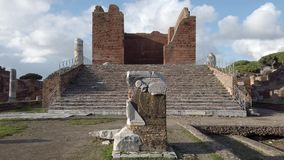 Landscape at Roman archaeological excavations of Ostia Antica with the Capitolium surrounded by ruins, columns and remains of stat. Ues stock video