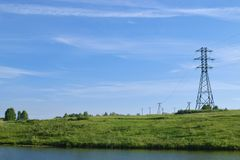 Landscape with row of electric poles over wild river across meadow with clear sky. Nature blue cable danger electrical electricity energy field high industrial royalty free stock photo