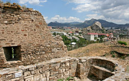 The landscape with the ruins of the medieval Genoese fortress in the foreground, the distant town and far mountains. Stock Image