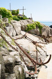Landscape with a rusty anchor, chains, rocks, green bushes in the city of Sozopol, Bulgaria Royalty Free Stock Photo