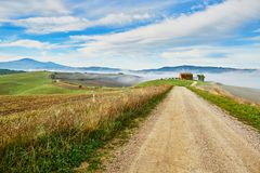 Landscape of San Quirico d`Orcia, Tuscany, Italy. Scenic Tuscan landscape with beautiful fields, meadows and hills with morning fogs. San Quirico d`Orcia Stock Photo