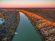 Landscape of sandstone cliffs over Murray RIver and moored houseboat at sunset. Stock Photo
