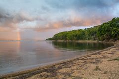 Landscape with sandy beach, dramatic sky, rainy clouds and rainbow. Royalty Free Stock Photography