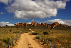 Landscape- sandy desert road. Country unsurfaced road to rhe yellow red cliffs. Yellow sand and green bushes, deep blue cloudy sky. Mountains of South Africa Stock Photography