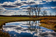 Glacial Park, Ringwood, IL In Autumn Hues. Landscape scene of bare trees and fluffy white clouds reflected in still blue waters of Nippersink Creek bounded by stock images