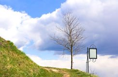 Landscape scenery with empty signboard. Hill, turning path, bare tree, sky with clouds and empty small decorated billboard with free space for your text during stock photo