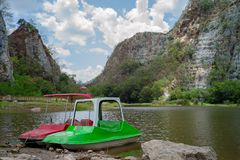 Landscape scenery of limestone mountain with the cloud and blue. Sky in background.Paddle boat parking in the lake with rocky mountain in background royalty free stock photo