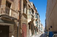 Malta, Valletta - Scenic, narrow street with old buildings. Landscape of the scenic narrow street with old buildings and traditional wooden, colorful balconies Stock Images