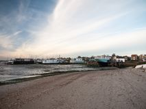Landscape sea front house row in distance beach. West mersea, essex, england, uk stock photos