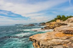 Landscape of the sea with rocks in the foreground and islands and blue sky stock photo