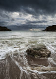 Landscape of sea storm approaching beach with rocks in foregroun Royalty Free Stock Photography