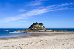 Landscape, seascape with beach and a house on top of a rock. Royalty Free Stock Image