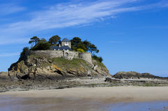 Landscape, seascape with beach and a house on top of a rock Royalty Free Stock Images