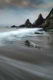 Landscape seascape of jagged and rugged rocks on coastline with Royalty Free Stock Photos