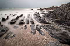 Landscape seascape of jagged and rugged rocks on coastline with Royalty Free Stock Image