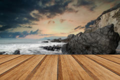 Landscape seascape of jagged and rugged rocks on coastline with. Rugged long exposure landscape seascape of rocky coastline with wooden planks floor Royalty Free Stock Images