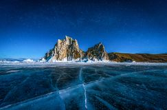 Landscape of Shamanka rock and star on sky with natural breaking ice in frozen water on Lake Baikal, Siberia, Russia.  stock photo