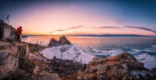 Landscape of Shamanka rock at sunset with natural breaking ice in frozen water on Lake Baikal, Siberia, Russia.  royalty free stock photo
