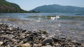 Landscape shooting of pebbles, oncoming waves and mountains. A close up shot of a surf on a pebble beach against the backdrop of mountains and a blue sky stock footage