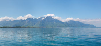 Landscape. Shore of the lake and snow capped mountains on a sunny day Royalty Free Stock Photo