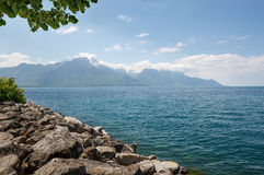Landscape. Shore of the lake and snow capped mountains on a sunny day Stock Photography